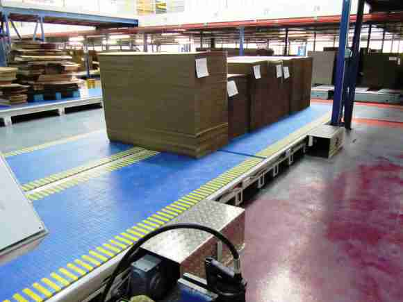 Heavy duty modular flat belt transports stacked corrugated cardboard