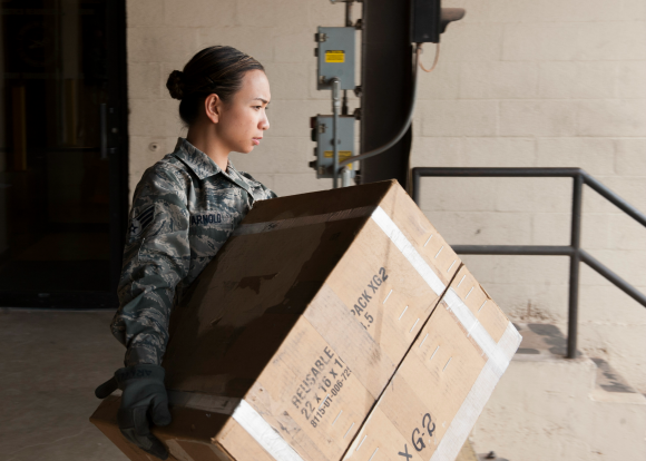 Reusable Container Program includes corrugated, wood and plastic containers. U.S. Air Force Senior Airman Giorgiamikaela Arnold, 7th Logistics Readiness Squadron B-1 Aircraft Part Store technician, carries a cardboard reusable container. Containers. The Reusable Container Program is designed to meet DoD policy by ensuring every part, stored or shipped, has the appropriate container. (U.S. Air Force photo by Airman Quay Drawdy/Released)